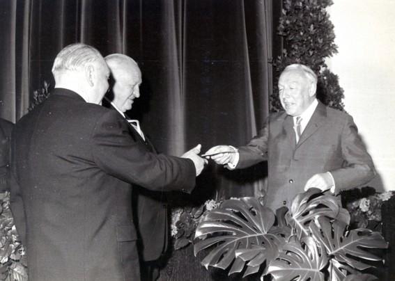 Regierungspräsident Dr. Friemann (rechts) überreicht den Erlass über die staatliche Anerkennung